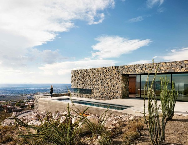 Modern home with outdoor, swimming pool, lap pool, small pool, concrete pool, back yard, slope, and desert. The main level of the Franklin Mountain House is built with volcanic rock basalt and granite from the region. Photo 2 of West Texas Vistas