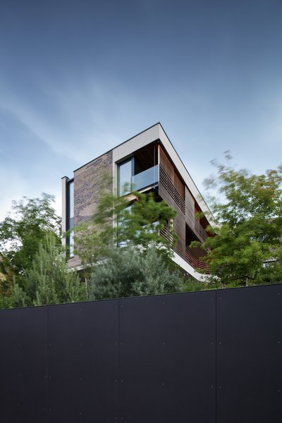 Modern home with outdoor, trees, and metal fence. Photo  of Villa H