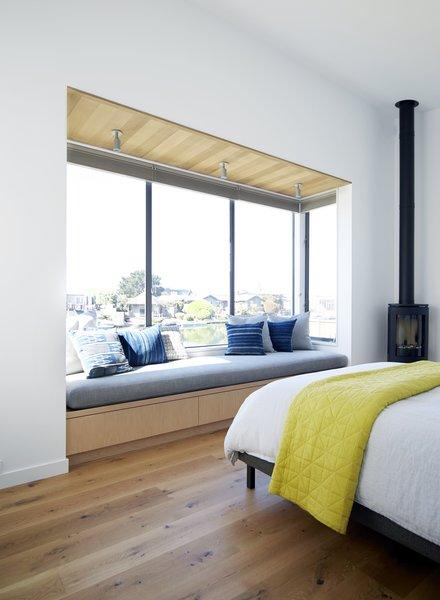 #TurnbullGriffinHaesloop #interior #bedroom #windowseat #woodburningstove   Photo 10 of Stinson Beach Lagoon Residence modern home