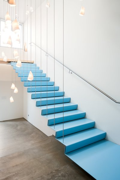 Floating stairs to the boardroom are framed by over forty porcelain 21 series pendants by Bocci.