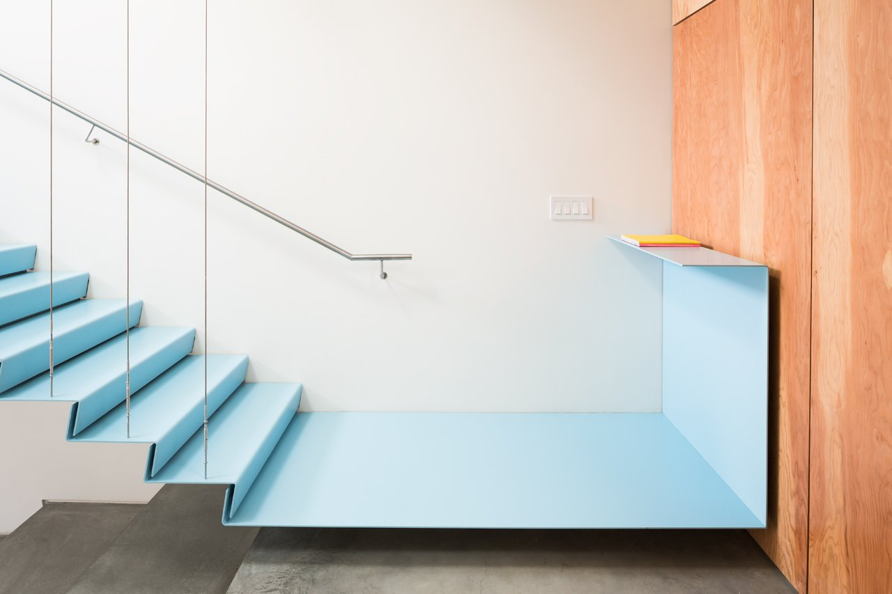 The staircase has a floating metal landing that connects to a fir plywood wall.