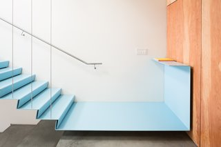 A Creative Agency with a Modern, Open Workspace - Photo 3 of 9 - The staircase has a floating metal landing that connects to a fir plywood wall.