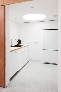 A Creative Agency with a Modern, Open Workspace - Photo 5 of 9 - The kitchen has a low ceiling with an inset circular skylight that creates a tubular glow.