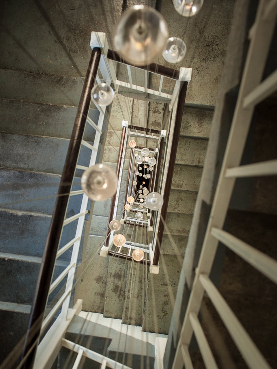 120 glass pendants from Bocci's 14-series illuminate the back staircase.  Photo 6 of 8 in Inside the Head Office of Bocci