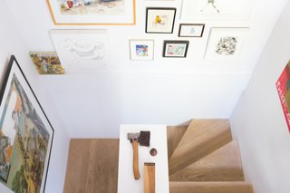 A Revitalized Townhouse that Owes Everything to Angles - Photo 3 of 8 - The whitewashed oak staircase, flanked with a salon-style art display.