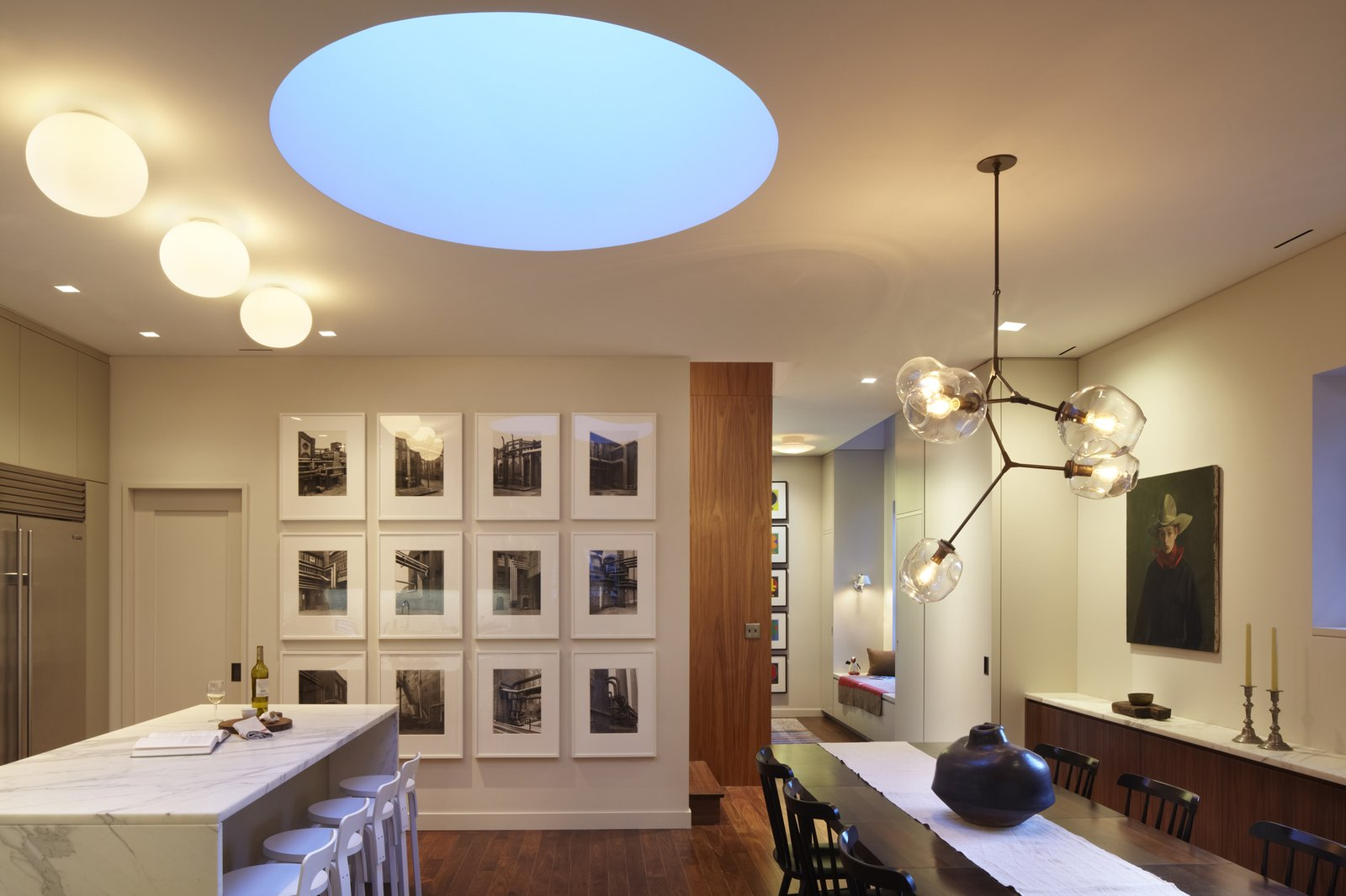 This photo shows the changing color temperature of the drum skylight.  Here at dusk when the light turns a beautiful blue.  The photo also highlights our use of multiple styles of architectural lighting: tape-in recessed LED downlight, surface mounted and pendent fixtures combine to create a warm modern environment. White Street Residence by pulltab
