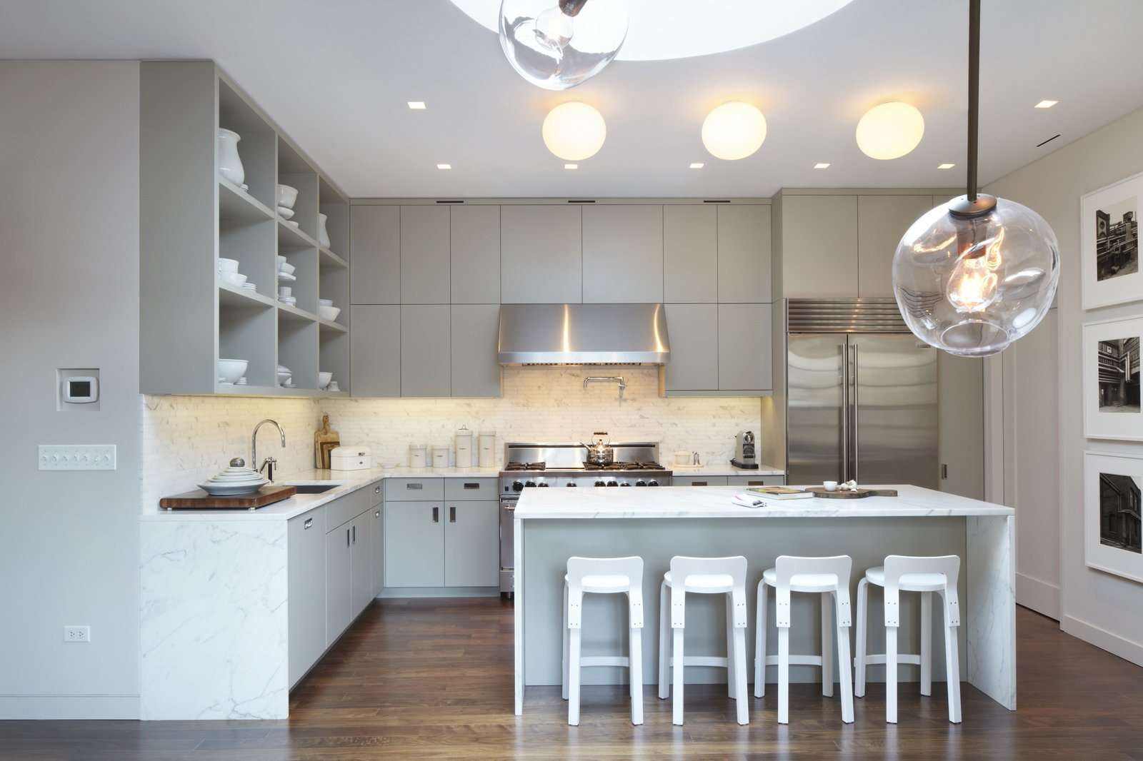 An overall photo of the kitchen with the Bernd and Hilla Becher photograph series on the right.  The drum skylight can be seen above and in the foreground are branches of a Lindsey Adelman pendant which hangs over the dining table.