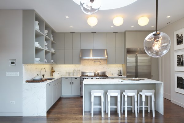 An overall photo of the kitchen with the Bernd and Hilla Becher photograph series on the right.  The drum skylight can be seen above and in the foreground are branches of a Lindsey Adelman pendant which hangs over the dining table. Photo 2 of White Street Residence modern home