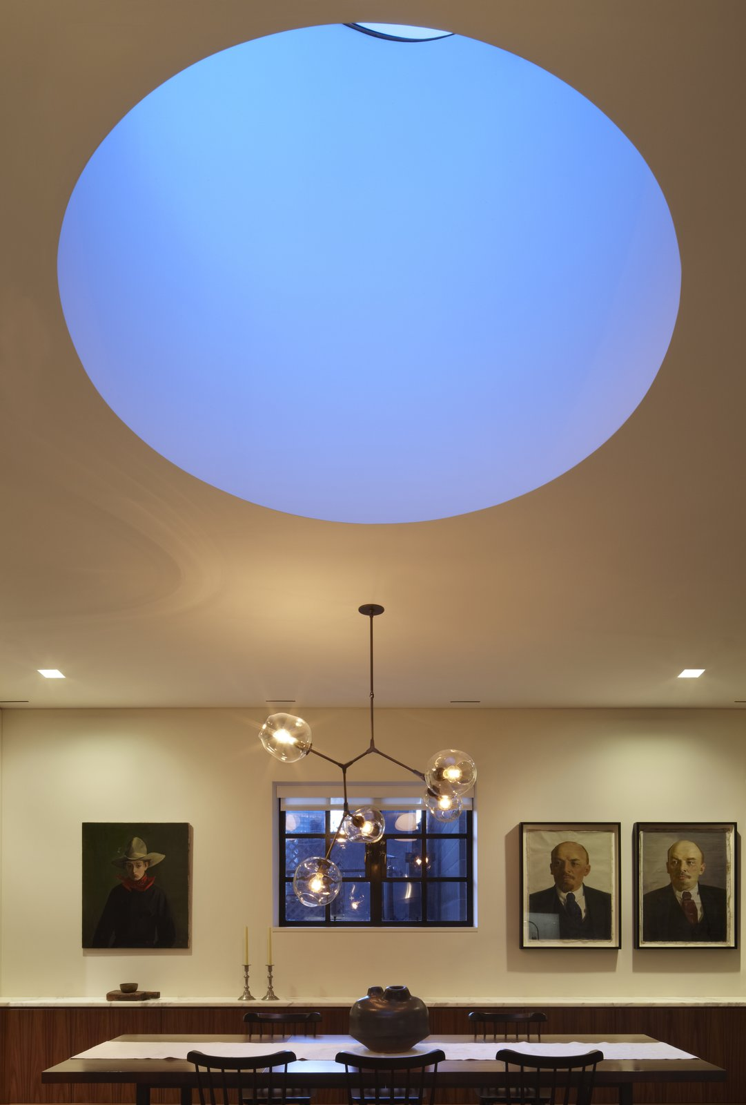 A view of the drum skylight at dusk.  Early in the design process we discussed with our clients the work of James Turrell including a field trip to Meeting at MoMA PS1 on a very cold but wonderfully quiet day.  One of the things we really like about Mr. Turrell's work is the flattening of perspective while creating a meditative balance between lightness and weight.  Here the drum skylight while physically large recedes into the ceiling plan