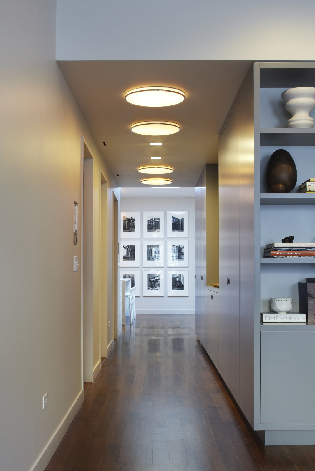 The front hallway links the living room to the kitchen and dining area.  The existing apartment was originally a manufacturing loft space.  NYC lofts being long and narrow with windows typically only at the front and rear façades can be somewhat dark.  With this in mind we designed the apartment to have light filled spaces via rooftop skylights.  Here a photo series by Bernd and Hilla Becher are washed with natural light from a large drum skylight not yet visible from this perspective.  The hallway ceiling echoes the drum skylight with Munkegaard fixtures, one of our favorites from Louis Poulsen.