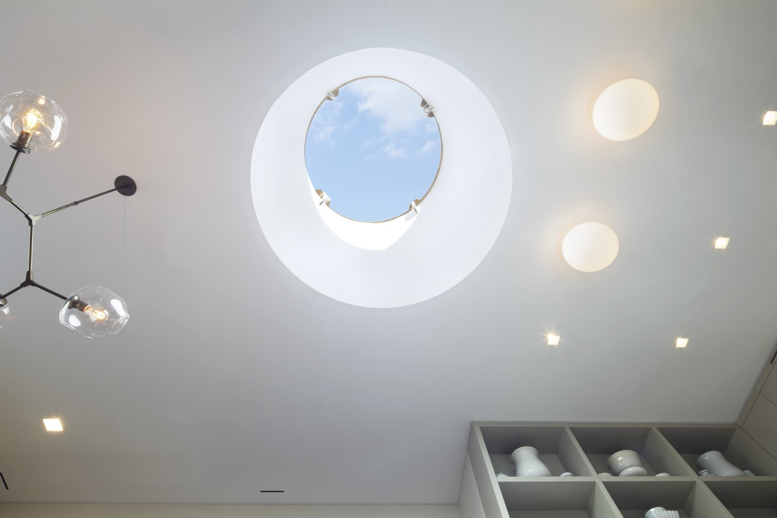 Looking up into the 5' wide drum skylight in the White Street Residence - remote controlled synchronized linear actuators open and close the skylight which allowed us to meet the NYC Code for legal light and air.  A beautiful Lindsey Adelman Branch chandelier is on the left and Flos Glo Ball fixtures paired with USAI Bevel trimless fixtures are on the right.