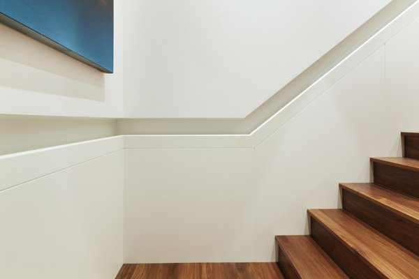 A detail photo of the inset handrail.  The lower panels and handrail are fabricated from Glacier White Corian - above the handrail is skim coated drywall painted to match.  The handrail runs continuously from the lower floor to the penthouse. Photo 8 of White Street Residence modern home