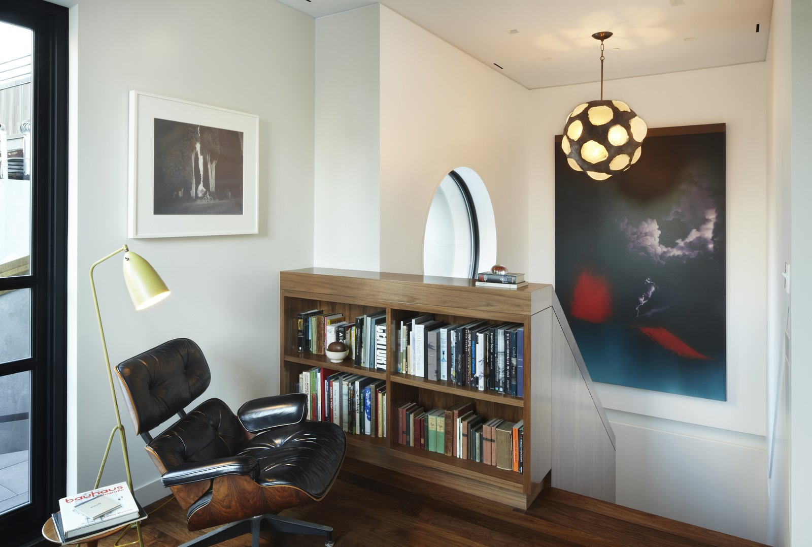 The upper landing in the White Street Residence provides a pausing point when going to and from the roof garden.  A walnut bookshelf, an extension of the walnut knee wall below stores a collection of the owner's art books.  The large circular window which overlooks the roof garden can be seen in the background. A vintage Grasshopper floor lamp by Greta Grossman provides reading light while relaxing in the Eames 670 lounge chair.