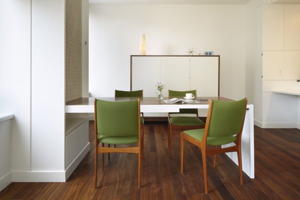 A side view of the fold-down dining table.  The table uses counterweights, concealed behind the Maharam fabric panel and was sized specifically for the apartment's ceiling height, comfortably seating four people. Photo 10 of Riverside Residence modern home