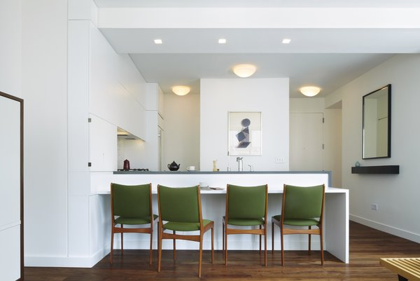 An overall view of the kitchen & dining counter.  Lighting alignments play a key role in our projects - here tape-in recessed lighting and surface mounted ceiling fixtures are centered on the kitchen and entry helping to frame a beautiful lithograph by the Belgian artist Pol Bury. Photo  of Riverside Residence modern home