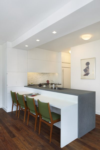 A three-quarter view of the kitchen and breakfast area.  The lower seating area countertop is Glacier White Corian and the upper counter is Atlantic Bluestone.  The chairs are vintage and reupholstered in Brushed Merino Sprig by Maharam. Photo 3 of Riverside Residence modern home