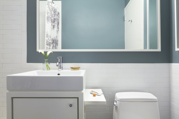 Space is at a premium in NYC bathrooms.  To maximize this space we created a concealed fold-up shelf as part of this custom Corian vanity.  This gives the owner an extra shelf on which to place items when needed but easily folds down to help keep an open feel to the room. Photo 17 of Riverside Residence modern home