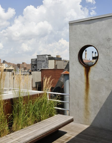 The garden is accessed from a rooftop penthouse designed by pulltab and built two years earlier.  A large diameter steel pipe was cut and placed into a new stucco wall.  This aperture frames a view to a power plant located on the Lower East Side.  The steel ring was left unpainted so it can rust and bleed down the wall.   The floating bench is made from Cor-Ten steel and teak which is left to weather a beautiful grey. Photo  of East Village Roof Garden modern home