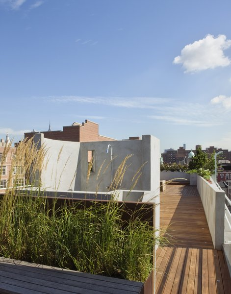 A view from the entry to the roof deck toward the outdoor shower.  The shower wall has an opening which frames the New York Life Insurance Building which can be seen in the distance. Photo 2 of East Village Roof Garden modern home