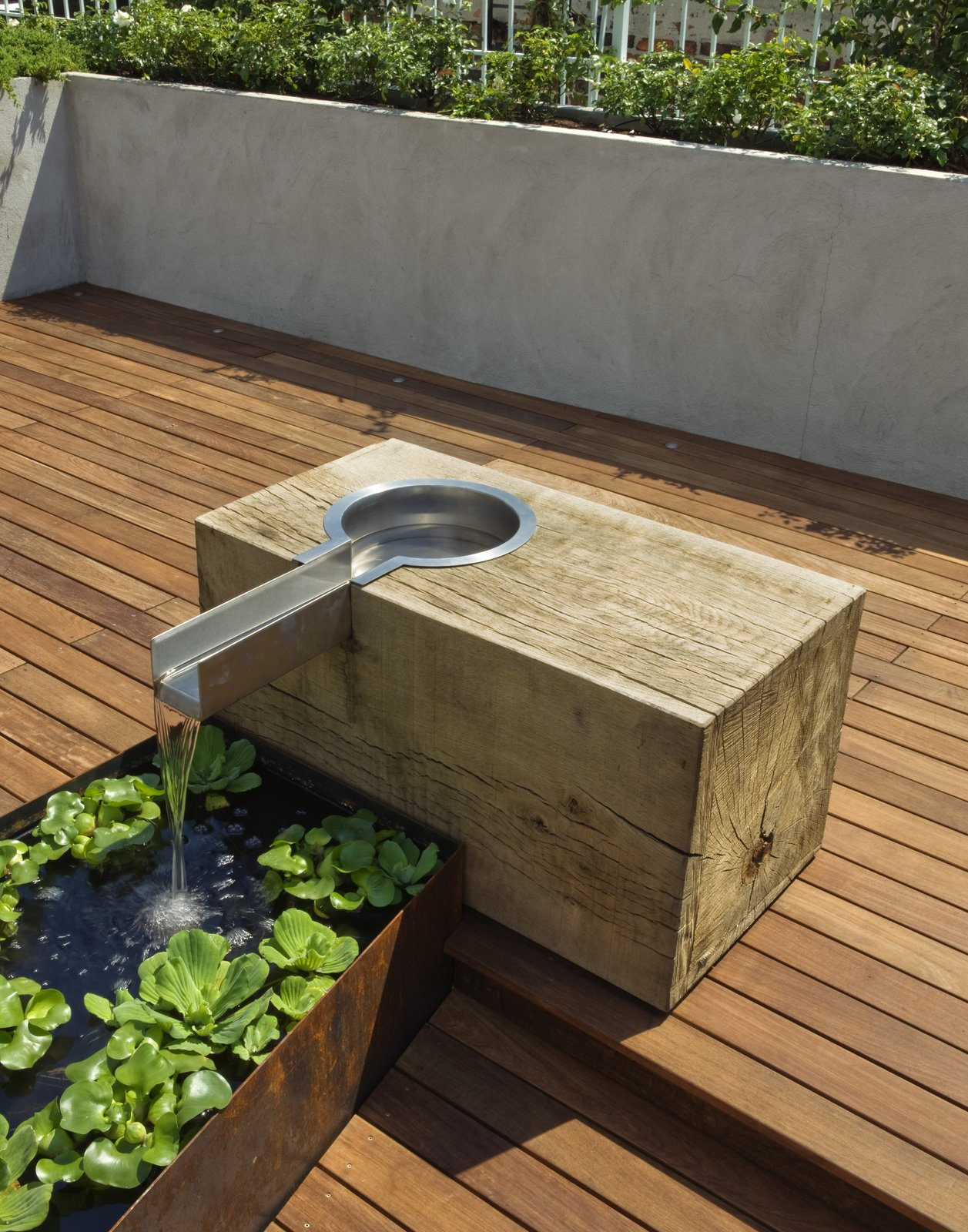The oak block was sourced from a mill outside of Philadelphia.  The block was rough sawn and left unfinished to weather and develop a patina.  The lined water trough is fabricated from Cor-Ten steel.
