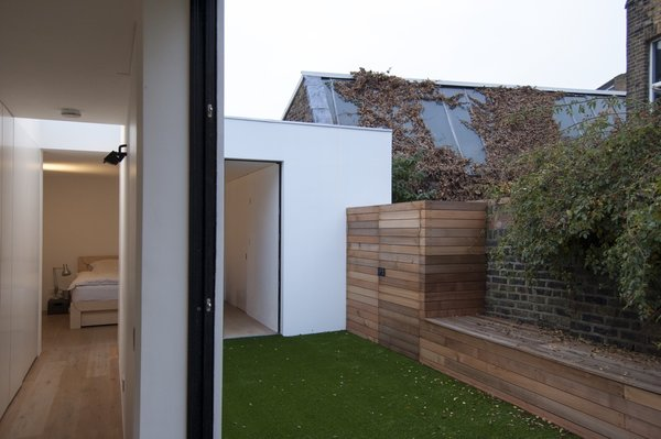 The master bedroom and bathroom can be viewed across the courtyard from the galley kitchen that occupies the glazed link. Photo  of Unité de Rénovation modern home