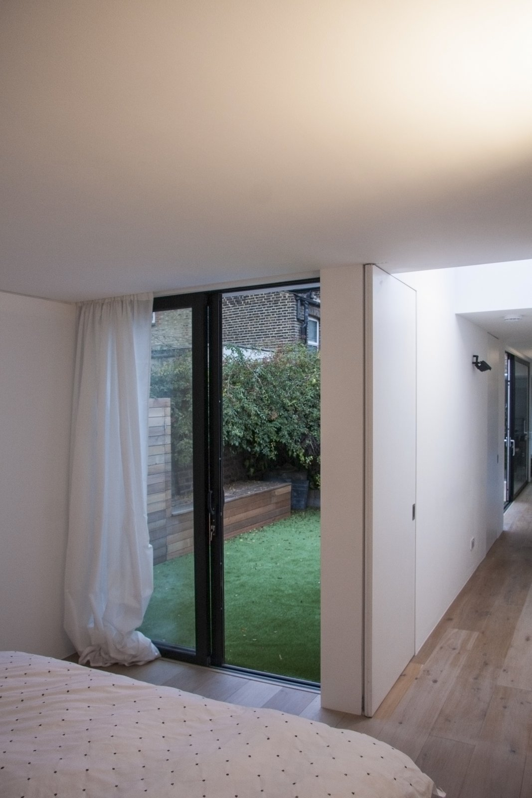 From the master bedroom one can look back down the length of the space through the internal kitchen link or the external courtyard.