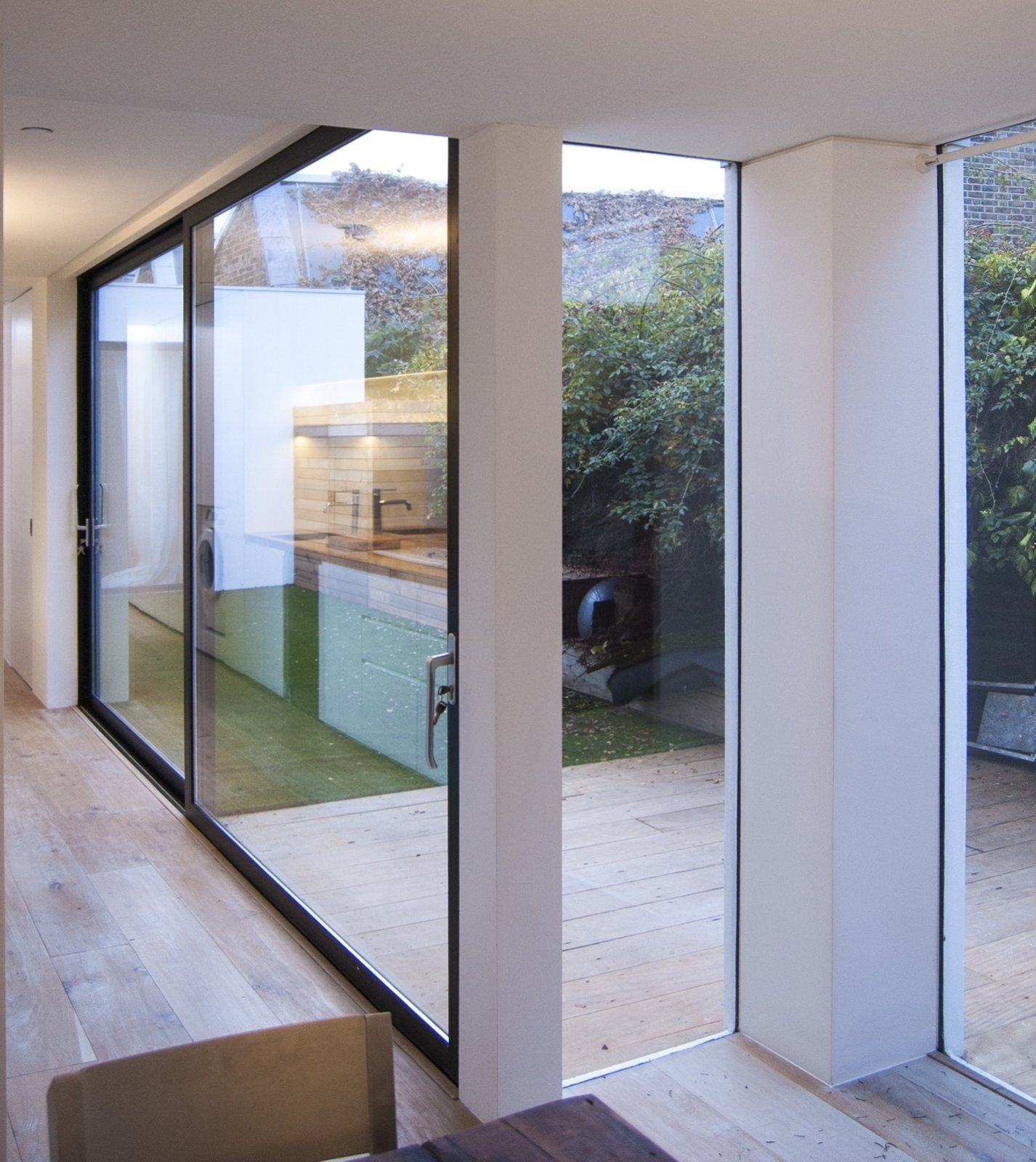 The dining area is open-plan to the kitchen and living space and separated from the courtyard by large panels of fixed glazing.  Unité de Rénovation by WILLIAM TOZER Associates