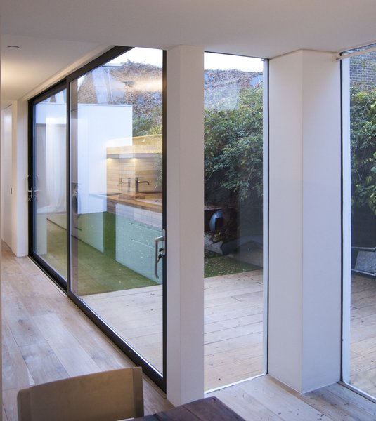 The dining area is open-plan to the kitchen and living space and separated from the courtyard by large panels of fixed glazing. Photo 8 of Unité de Rénovation modern home