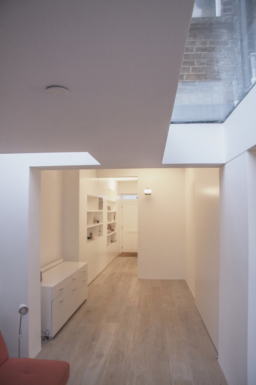 Roof-lights provide views of the sky and loosely delineate the living space from the adjacent entry and dining spaces.