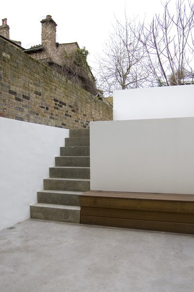 A concrete staircase connects the lower courtyard to the raised garden area, both framed by exterior walls and planters that extend the interior vocabulary into the exterior spaces. Photo  of Periscope modern home