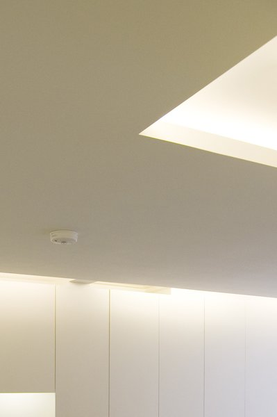 A lowered ceiling conceals fluorescent lighting and enhances the perception of the design as a delicately attached modern architectural intervention. Photo 3 of Periscope modern home