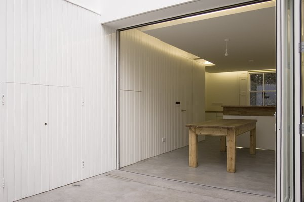 Referencing a traditional building element but using modern detailing, the white-painted wall panelling is continuous from inside to outside. Photo 7 of Periscope modern home