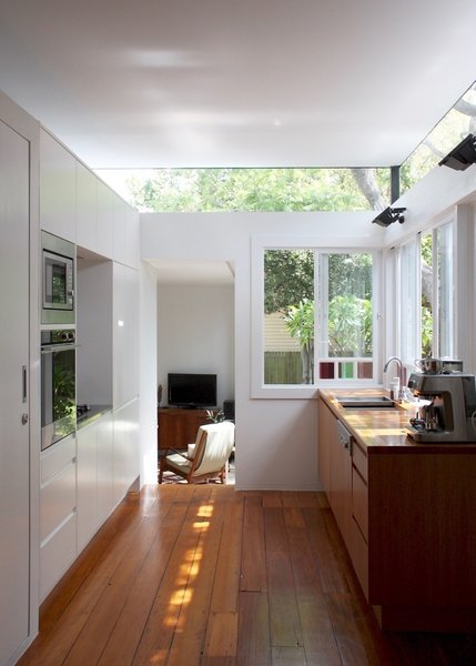 Looking from the open-plan dining area, through the kitchen to to the new living space, one gets views of the tree canopy through a high-level band of frameless glazing. Photo  of Villa Leichhardt modern home