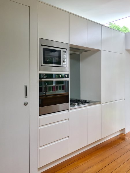 A white pod stops short of the full ceiling height, incorporating kitchen appliances and storage, and accommodating the bathroom. Photo 6 of Villa Leichhardt modern home