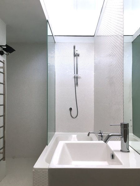 Inside the white pod, the white-tiled bathroom is top-lit by a glazed panel bringing in borrowed natural light from the high-level glazing in the kitchen. Photo 7 of Villa Leichhardt modern home