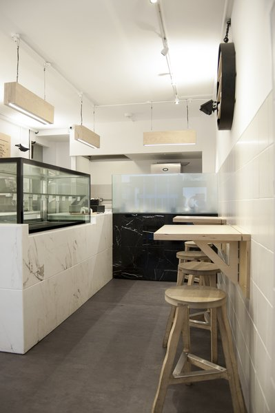 From the entry, visitors see the white and black marble sculptural volumes of the service counter and preparation areas, and the plywood lights and tables.  Photo  of Storefront for Cake and Architecture modern home
