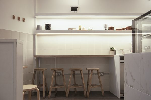 Floodlights create a general wash of background lighting, while concealed strip-lights highlight produce, products and serving dishes. Photo 4 of Storefront for Cake and Architecture modern home