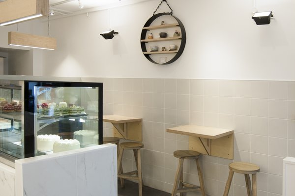 Tiles to the walls and vinyl to the floor are both continuous between the customer and staff areas, further blurring the boundary between the two and heightening the sense of involvement in the baking process. Photo 2 of Storefront for Cake and Architecture modern home