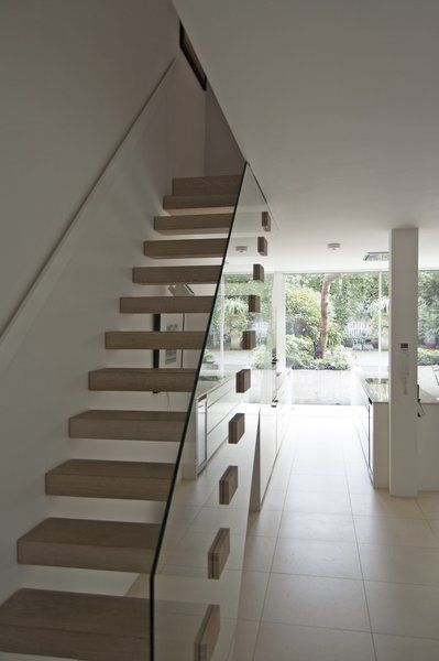 The modern lower-ground floor connects to the rest of the house via an open-riser timber staircase with clear glass balustrade.