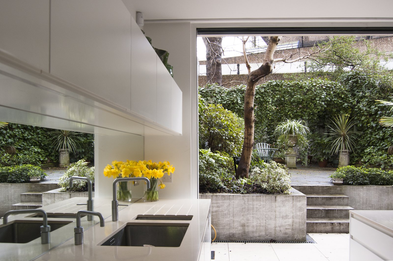 The brutalist council estate to the rear is viewed as a found-object artwork through a new cast-concrete and stark white frame. Tagged: Kitchen, White Cabinet, Mirror Backsplashe, Ceramic Tile Floor, and Undermount Sink.  Soupçon Brut by WILLIAM TOZER Associates