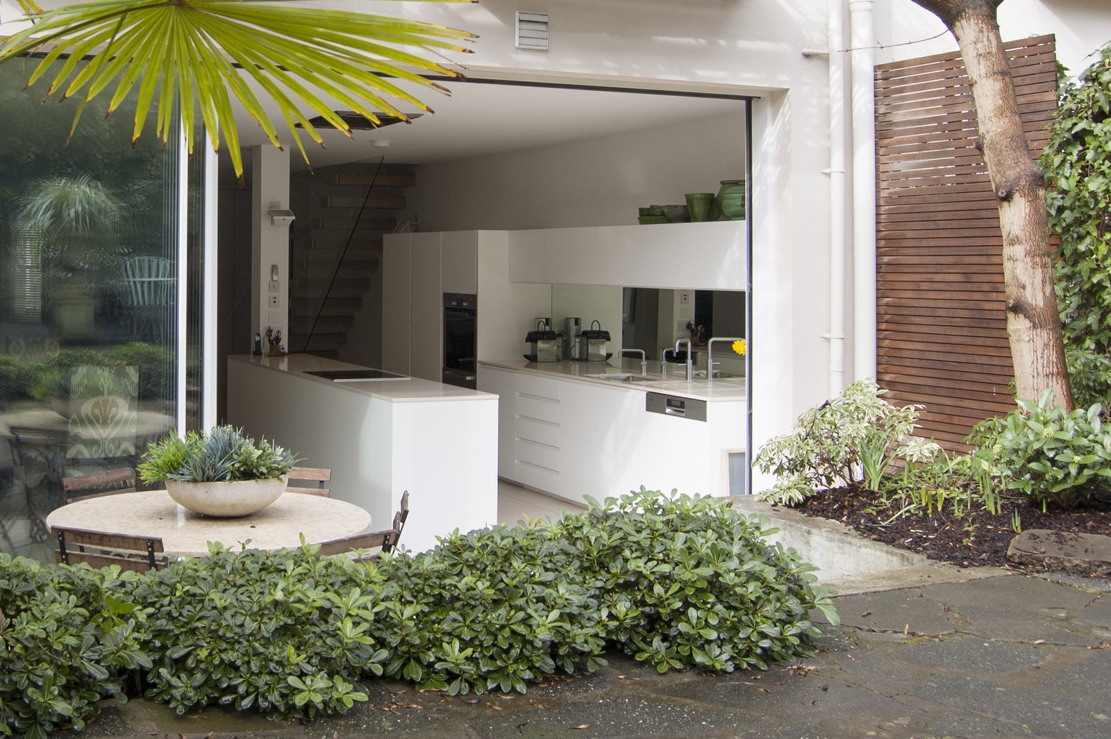 The modern intervention is articulated as a clean cut into the original building fabric, into which a sleeve of modern architecture is inserted. Tagged: Outdoor, Back Yard, Trees, Hardscapes, Raised Planters, Concrete Patio, Porch, Deck, Gardens, and Horizontal Fences, Wall.  Soupçon Brut by WILLIAM TOZER Associates