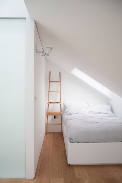 The top floor accommodates a glass-roofed shower, and a bedroom with its own small living space, top-lit by a motorized glazed roof and frameless roof-lights.