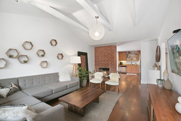 exposed beamed ceilings and original brick fireplace add to the ranch HAUS vibe Photo  of 2381 Elden Avenue modern home
