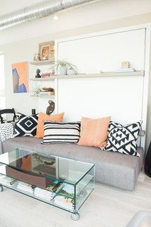 "The transforming wall bed system and accompanying glass coffee table by Resource Furniture modeled a space-saving solution for compact quarters. As the home travels from stop to stop, its furnishings evolve to conversate with the aesthetic of the host city. <span style=""line-height: 1.8;"">For San Francisco, Courtney Lake of Monogram Decor used a palette of blue, orange, and gold to evoke a youthful energy and recall the Golden Gate Bridge spanning bay waters.</span>"