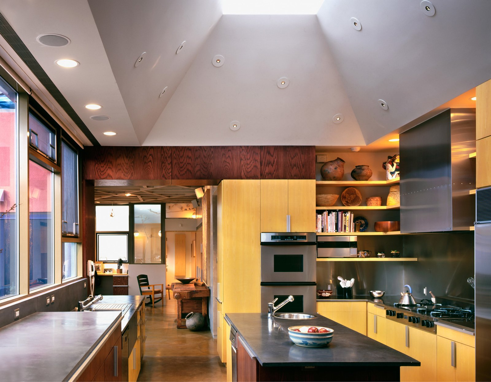 The kitchen features poured concrete counters, double convection ovens, and dual warming drawers and dishwashers.