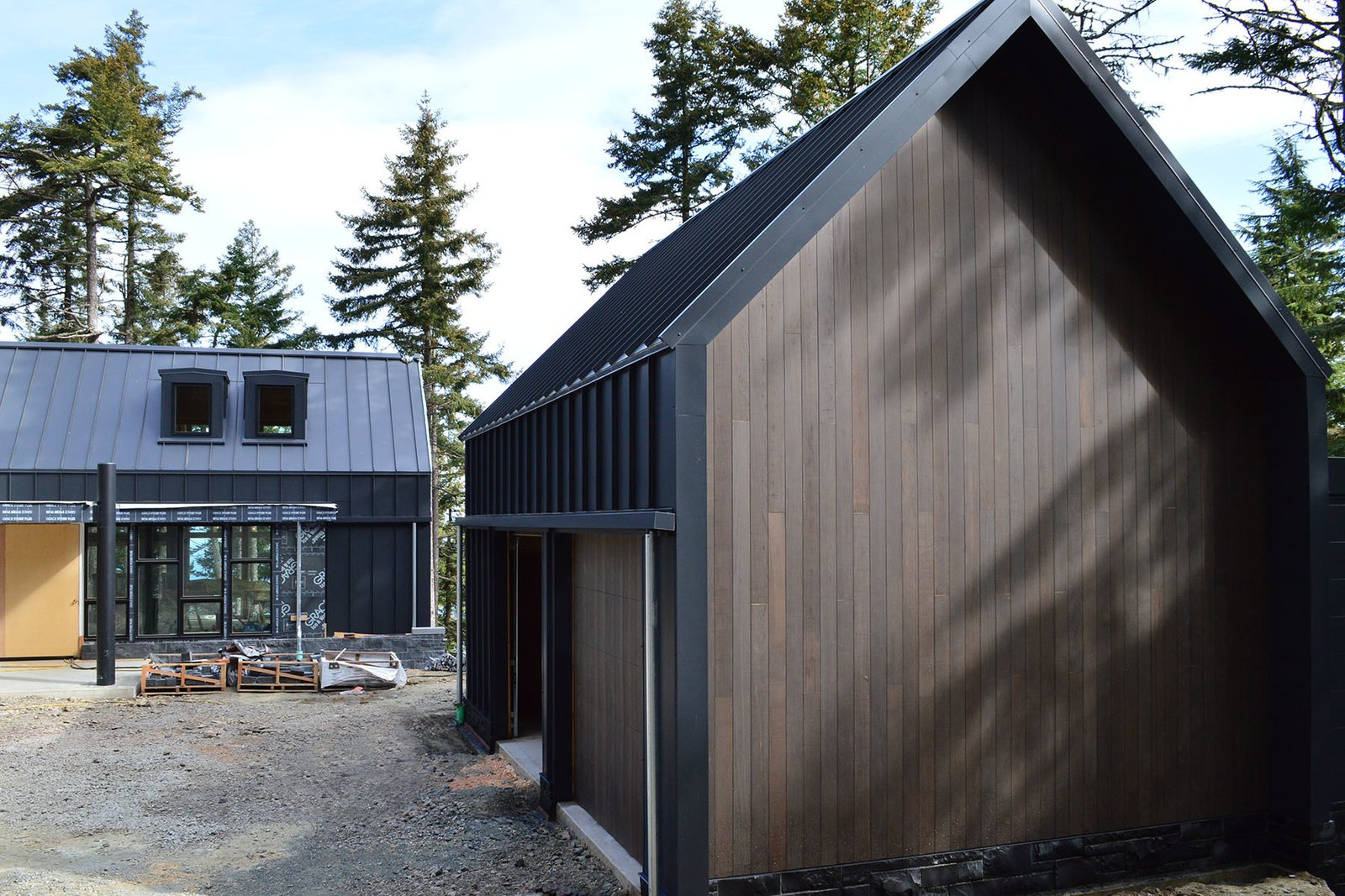 The garage exhibits the same black steel cladding and stained cedar siding as the main structure. Flat dormer windows on the house provide natural light and add visual interest to the overall shape. Paint it Black: One Couple's Journey to Minimalism - Photo 2 of 5