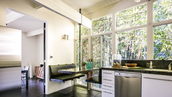 Booth seating in the eat-in kitchen creates a cozy nook behind a private bamboo fence.