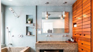 Own a Piece of Hollywood History for $1.995M - Photo 6 of 9 - Luxurious amenities outfit the master bathroom, where wood shelving provides a warm counterpoint to blue tiles and a concrete sink and tub.