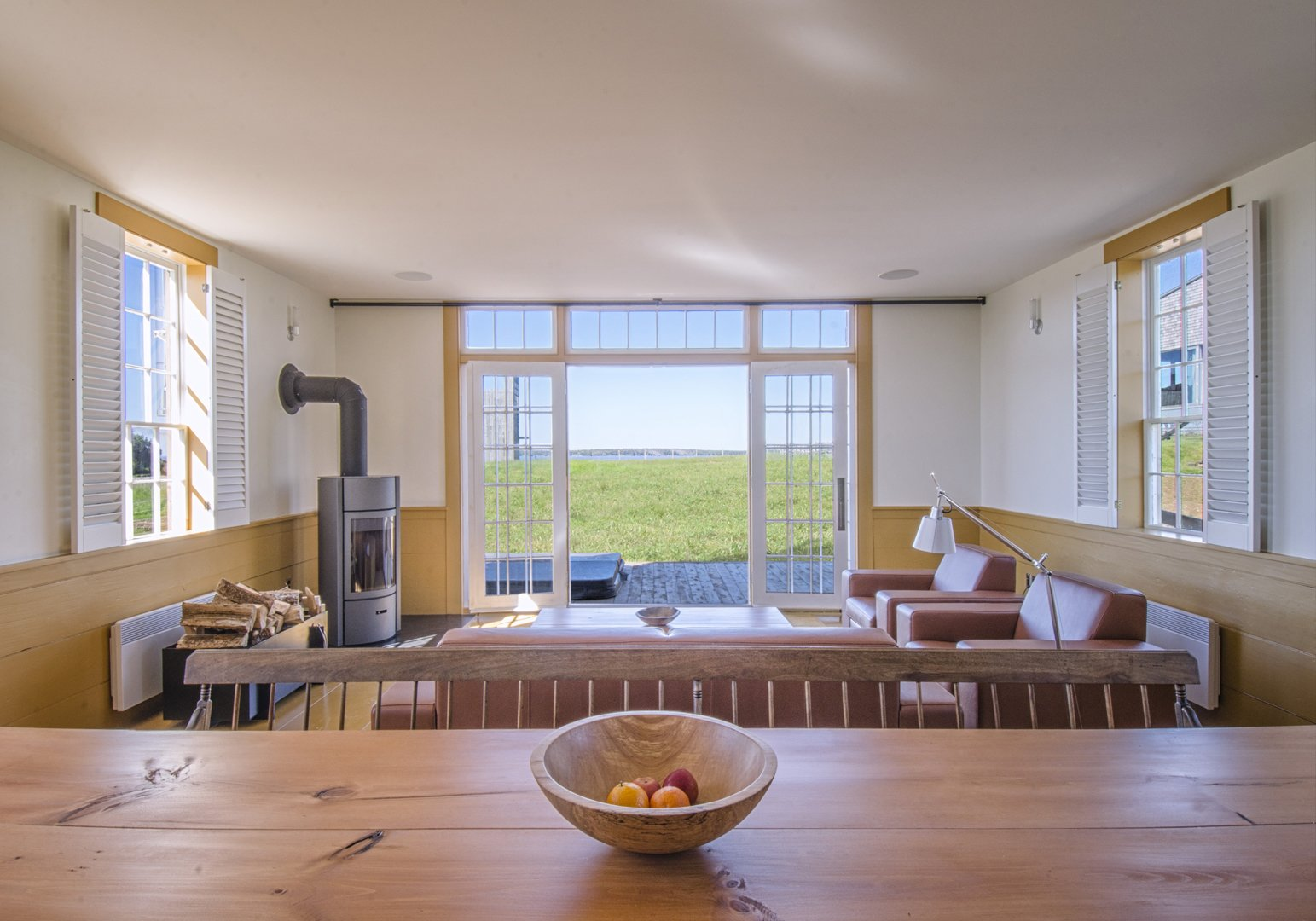 The open floor plan includes a kitchen with modern appliances, a half bath, and living and dining areas that open onto an outdoor terrace. A master bedroom and bunk room are upstairs along with a washer and dryer.  Photo 7 of 14 in Agrarian Pastime: Book a Village Stay in Nova Scotia