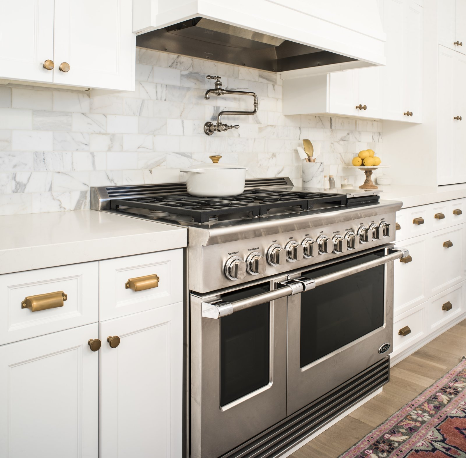 Dual Flow Burners deliver rapid, even heating that can reach up to 23,000 BTU, and the cooktop offers a total of up to 134,000 BTU.  The dials offer precise control with LED halos that turn white, orange, and red to indicate heating up, preheated, and self-cleaning modes, respectively.  Photo 3 of 8 in An Interior Designer's Streamlined Kitchen